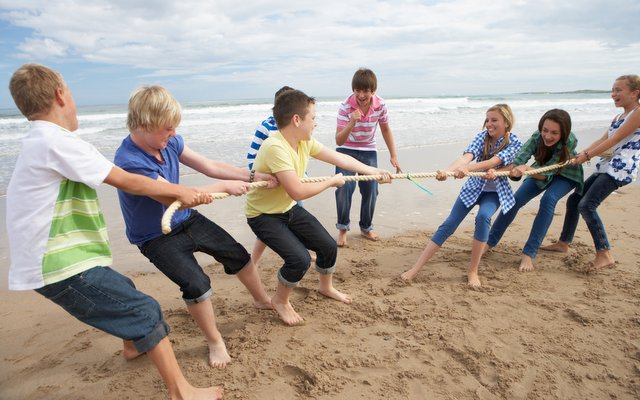Tug of war played by teens on a beach